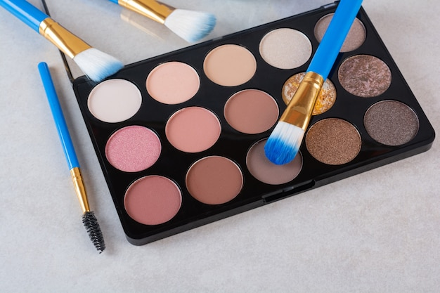 Make up brushes with foundation on grey.