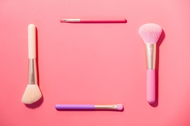 Кисти для макияжа с пудрой на розовом фоне