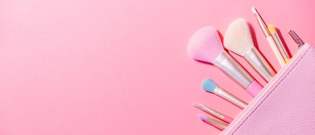 Кисти для макияжа с пудрой на розовой поверхности