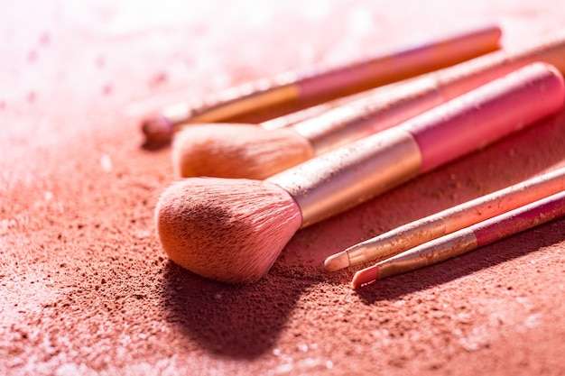Make up brushes with powder on pink background