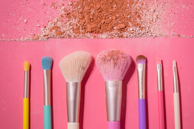 Make up brushes with powder on pink space