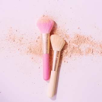 Make up brushes with powder on white surface