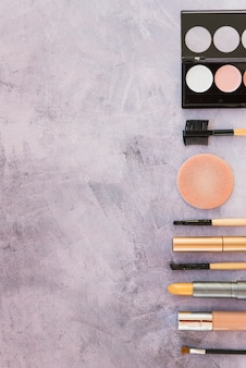 Make-up colorful eyeshadow palette with cosmetic products arranged in a row on concrete background