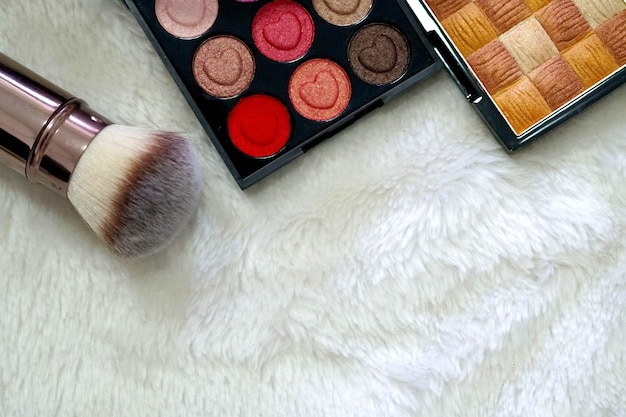 Make up cosmetic beautiful eyeshadow and brush on put on a white mink cloth background