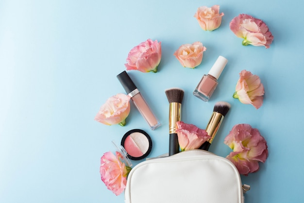 Make up cosmetics with pink flowers on blue