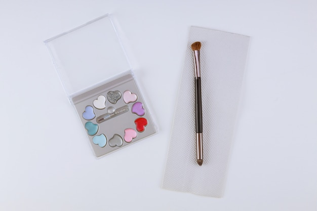 Make up eye shadow palette with brush on isolated white table