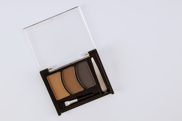 Make up flat lay multicolored eye shadow in the drawing eye lines on isolated white table