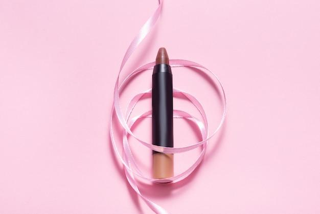 ピンクのリボンで飾られたピンクのテーブルに口紅を作る