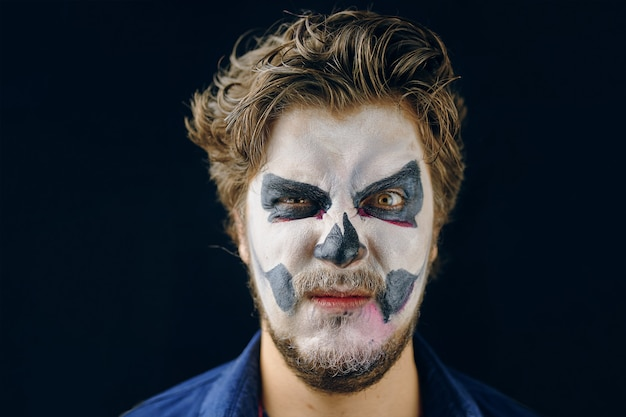 Make-up man of the day of death on halloween, evil suspicious glance. copy space