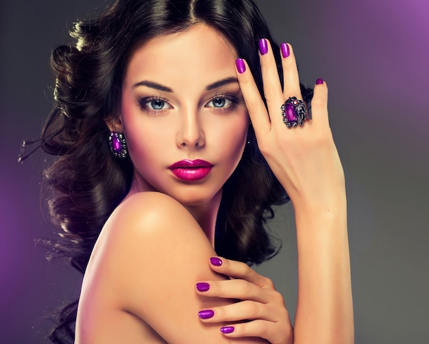 보라색 색조의 메이크업, 매니큐어 및 보석. 곱슬 곱슬하고 검은 머리의 여성이 얼굴에 보석 세트와 화려한 메이크업을 선보이고 있습니다. 미용, 화장품 및 스타일.