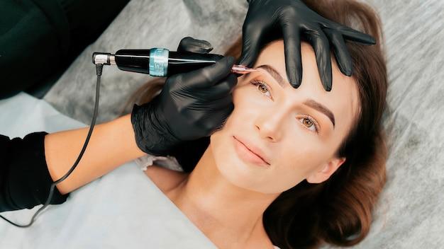 メイクマスターは、クライアントのために恒久的な眉メイクの手順を実行します