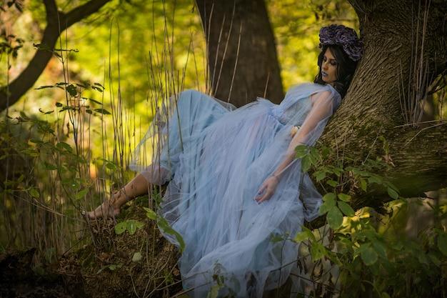 숲에 있는 나무에 누워 검은 머리에 웨딩 드레스를 입고 죽은 신부를 구성