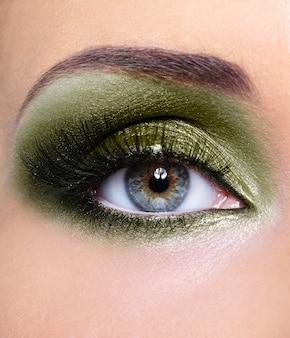 カーキ色のアイシャドウで女性の目のメイク