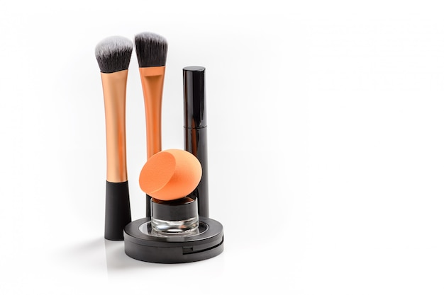 Make up powder, brushes, sponge and mascara background