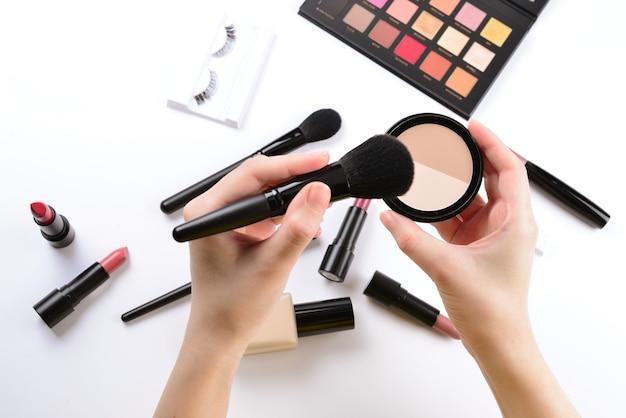 여자 손에 파우더 메이크업 화장품 미용 제품 파운데이션 립스틱 아이 섀도우 아이 속눈썹 브러쉬 및 도구가 포함된 전문 메이크업 제품