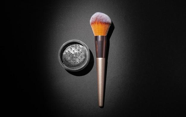 Пудра для макияжа с кистью на черном фоне, крупным планом