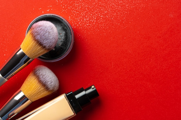 Make up products and cosmetics on red background. close up.