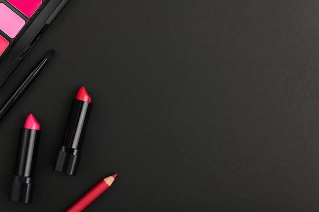 黒の背景に製品を作ります。上からのチークパレット、口紅、リップペンシル、ブラシ