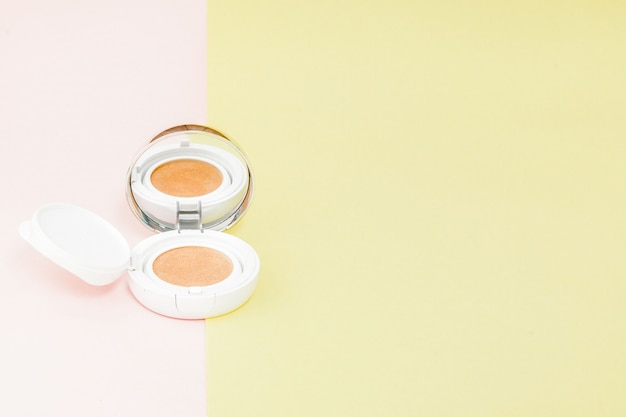 Make up products spilling on to a bright yellow and pink background with copy space