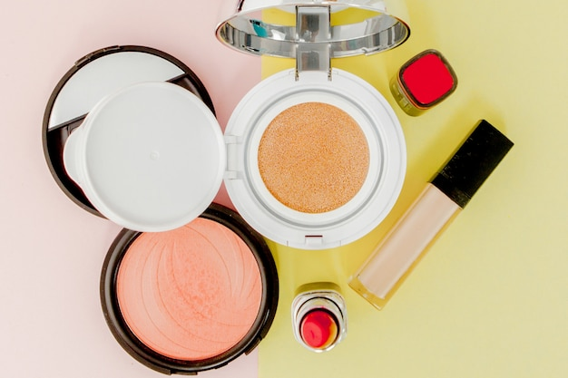 Make up products spilling on to a bright yellow and pink