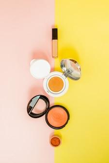 明るい黄色とピンクの背景にこぼれる化粧品