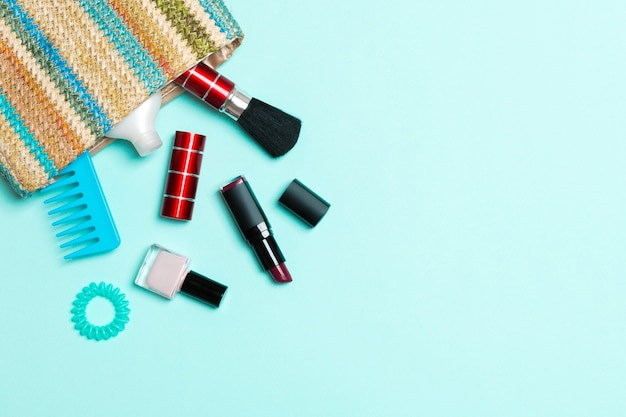 Make up products spilling out of cosmetics bag, on blue pastel background with empty space for your design.