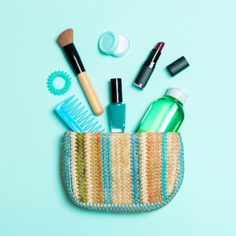 Make up products spilling out of cosmetics bag on blue pastel background with empty space