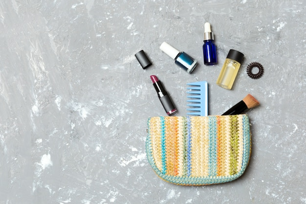 Make up products spilling out of cosmetics bag on grey cement background with empty space for your design