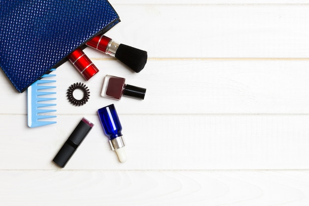 Make up products spilling out of cosmetics bag on white wooden background with empty space for your design.