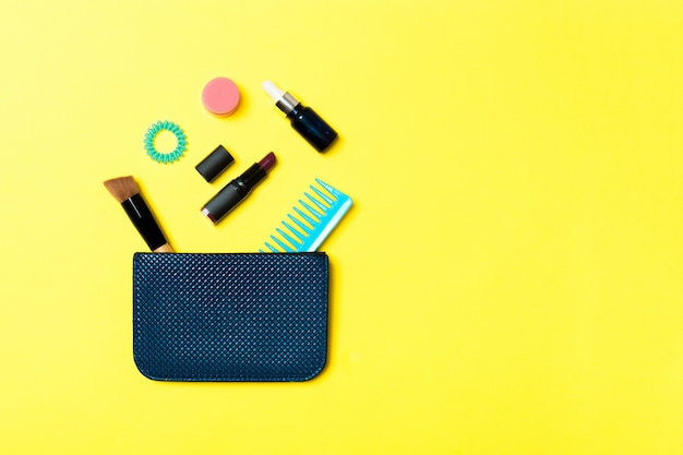 Make up products spilling out of cosmetics bag, on yellow background with empty space for your design