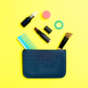 Make up products spilling out of cosmetics bag on yellow