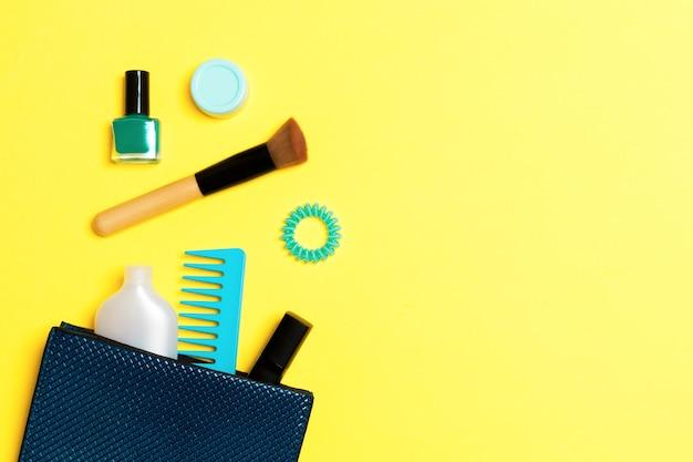 디자인을 위한 빈 공간이 있는 노란색 배경에 화장품 가방에서 쏟아지는 제품을 구성하세요.