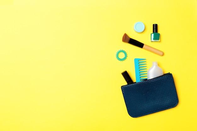 あなたのデザインのための空きスペースで黄色の表面の化粧品バッグからこぼれる製品を作ります
