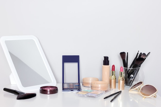 화장대에 거울이 있는 메이크업 제품. 메이크업 액세서리가 있는 화장대