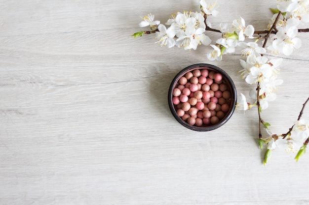 롤론 블러쉬 천연 화장품을 만들어 피부 관리를 위해. 나무 테이블에 꽃이 만발한 벚꽃의 장식. 미용 및 스파 개념