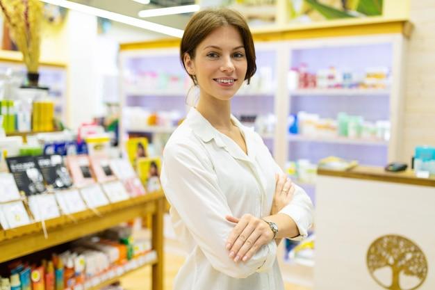 Молодая кавказская женщина в белой рубашке держа ее руки связанный в магазине make up и skincare