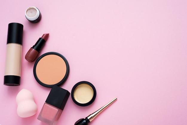 コピースペースでピンクの背景にツールや化粧品を作ります