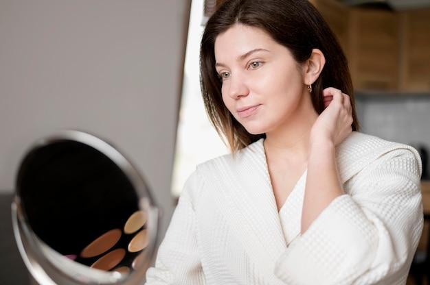 Maked женщина смотрит в зеркало