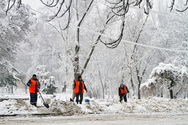 Makeevka, ukraine - 6 february 2020: communal services workers in uniform with shovels remove snow after a snowfall. weather collapse. editorial