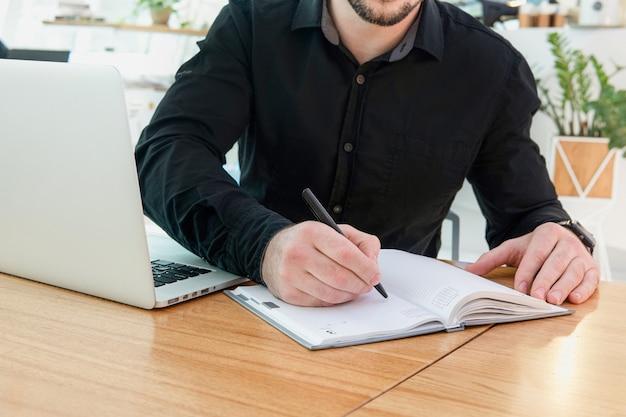 アポイントメントノートを作成し、重要なことややることリストを書きます。集中した男は机に座って、ペンを持って、スタートアップのビジネスのアイデア、計画、ノートブックのクローズアップ画像への創造的な考えを保ちます。