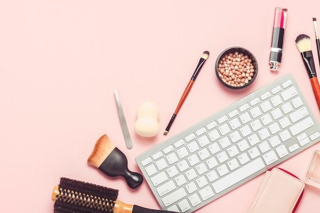 化粧と美容ツール、ピンクの背景のキーボード。オンライントレーニング、オンラインストアでの化粧品の注文、メイクアップ、テストのコンセプト。フラット横たわっていた、トップビュー