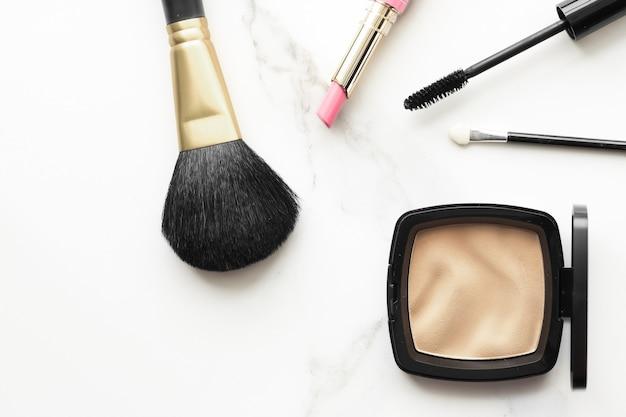 大理石のフラットレイの背景に化粧品と化粧品を使った、現代の女性らしいライフスタイルの美しさのブログとファッションのインスピレーションのコンセプト