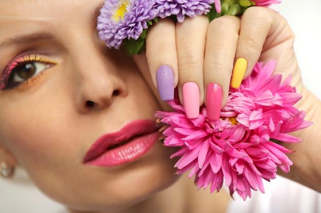 분홍색 과꽃을 가진 소녀의 긴 손톱에 메이크업과 매니큐어.
