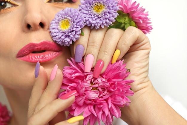 과꽃을 가진 소녀의 손톱에 메이크업과 매니큐어.