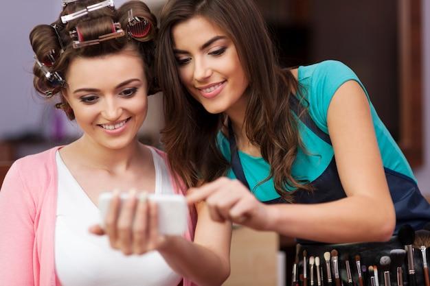 携帯電話で見ているメイクアップアーティストと女性の顧客