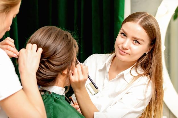 Визажист и парикмахер, работая со своей клиенткой в салоне красоты