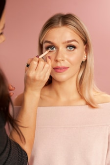 Makeup artist applied eyeliner pencil on a young blonde woman