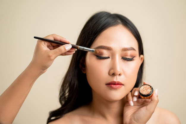 Makeup artist applied eyeshadow on the face of a beautiful asian woman.