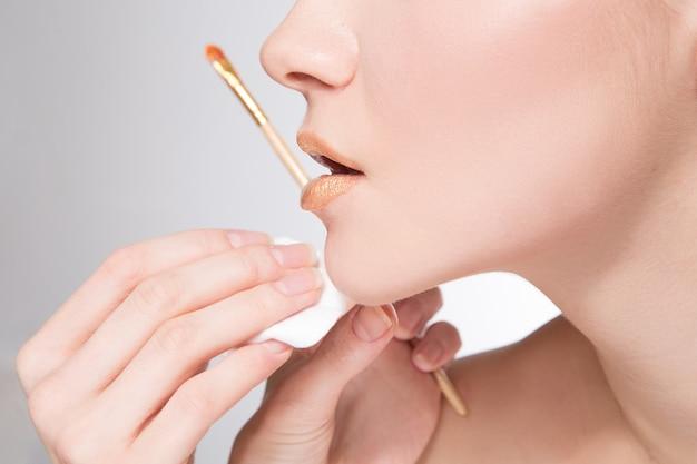 メイクアップアーティストは、ゴールドの口紅を適用します。美しい女性の顔。メイクアップマスターの手、若い美しさのモデルの女の子の唇を塗る