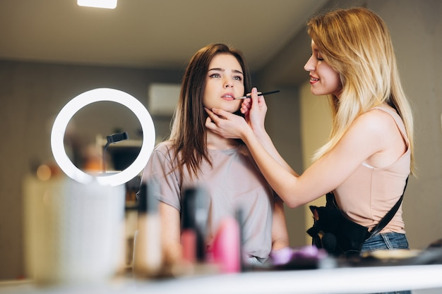 The makeup artist applies lipstick or gloss to the client's lips with a brush. the brunette and the blonde do makeup.